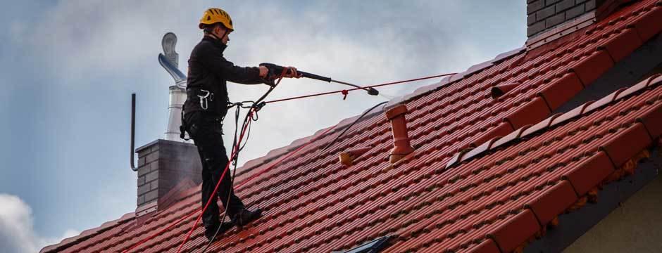 pracownik wysokościowy podczas mycia dachów, poprzedzającego malowanie dachów
