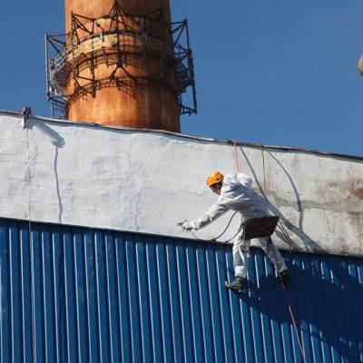 pracownik wysokościowy wykorzystując technologię natrysku hydrodynamicznego wykonuje malowanie elewacji