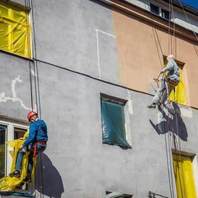 wysokościowe prace malarskie, pracownicy zabezpieczają folią okna i wykonują hydrodynamiczne malowanie elewacji