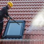 usuwanie zabrudzeń organicznych z dachu metodą ciśnieniową, pracownik wysokościowy myje dach, czyszczenie dachów odbywa się w Łodzi