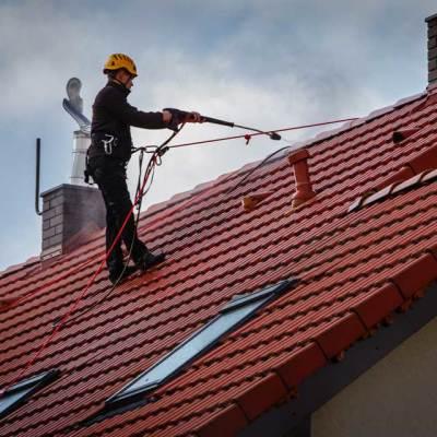 Pracownik podczas ciśnieniowego mycia dachów