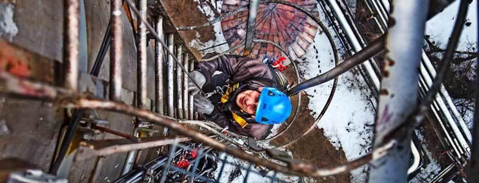 Alpinista przemysłowy wchodzi na stalowy komin. Malowanie i piaskowanie konstrukcji i stali w pracach wysokościowych