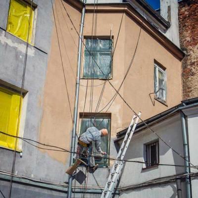 pracownik wysokościowy maluje elewację