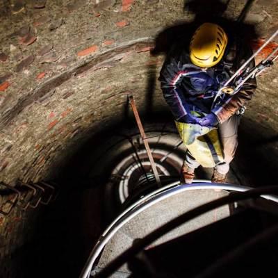 prace wysokościowe w kominie, alpinista przemysłowy podczas montażu dróg kablowych do oświetlenia przeszkodowego